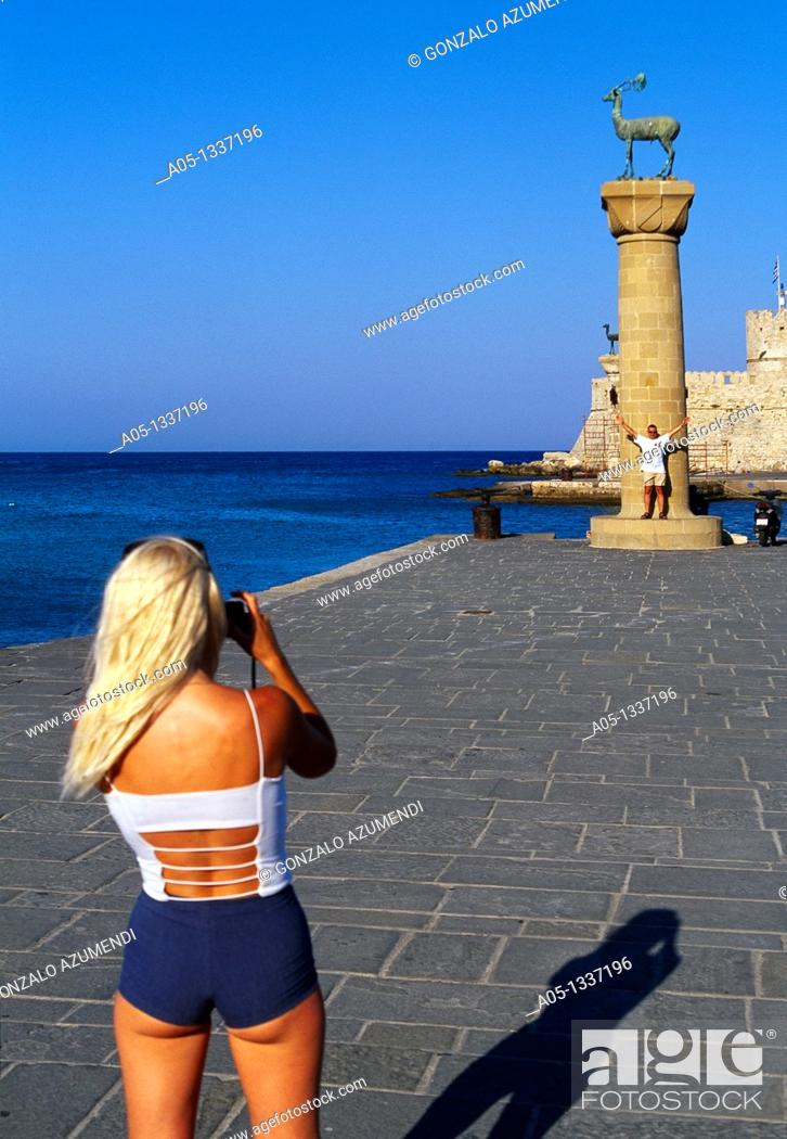 Stock Photo: Girl Takind pictures to stag column  Mandraki Harbour  Rhodes City, Rhodes Island, Greece.