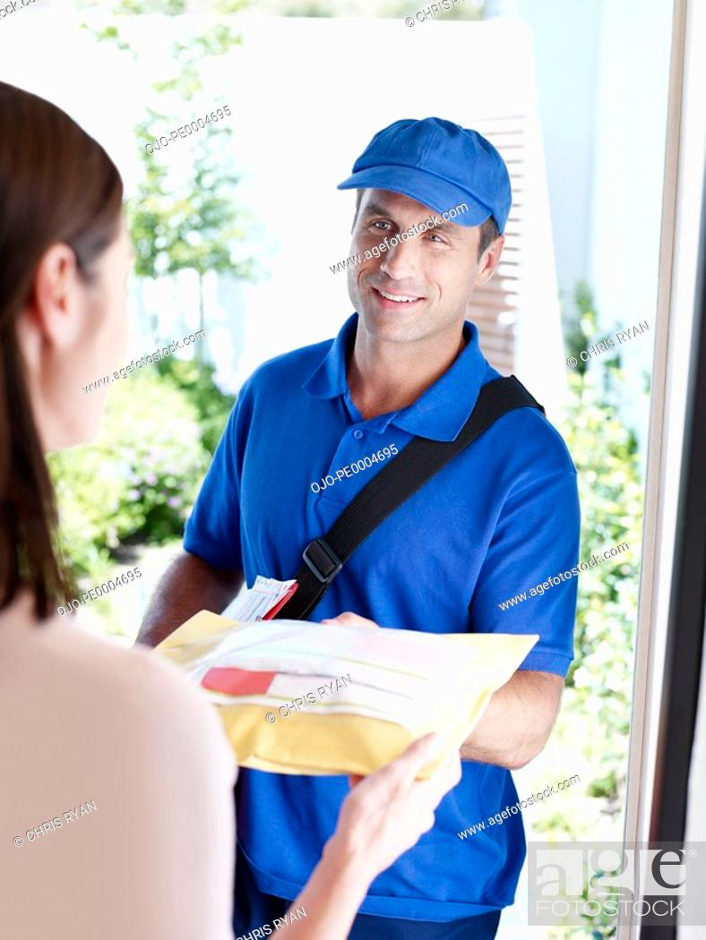 Photo de stock: Male delivery person giving package to woman.
