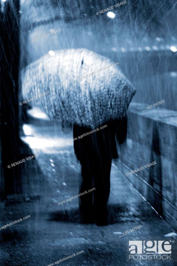 Stock Photo: Man with umbrella in the rain on the Ile Saint Louis. Paris. France.