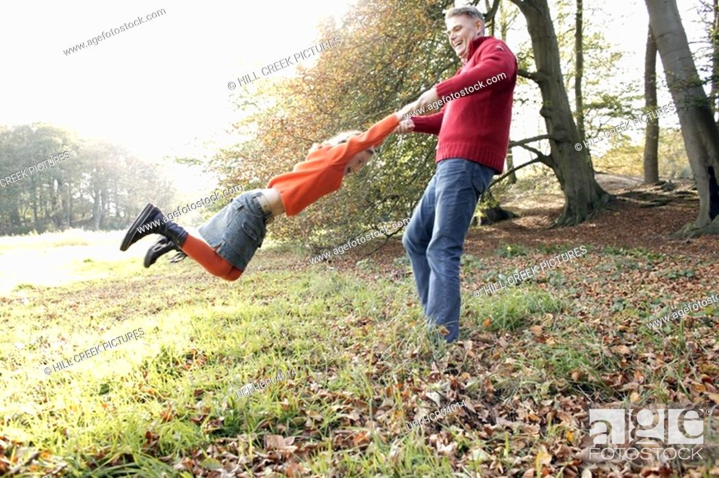 Stock Photo: Father swinging daughter.