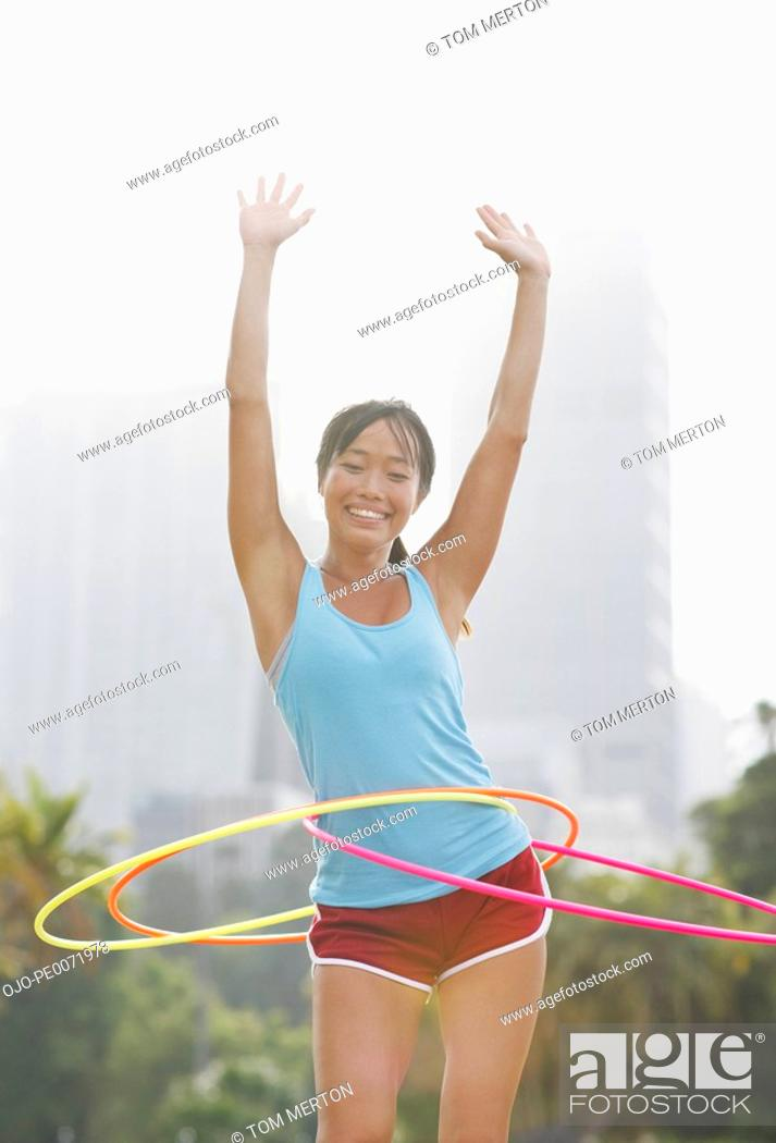 Stock Photo: Woman twirling hula hoops.