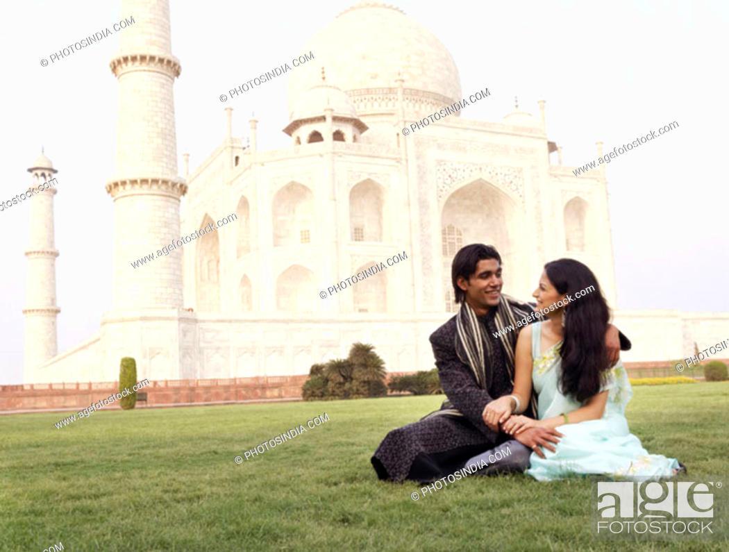 Stock Photo: Young couple sitting in front of a mausoleum, Taj Mahal, Agra, Uttar Pradesh, India.