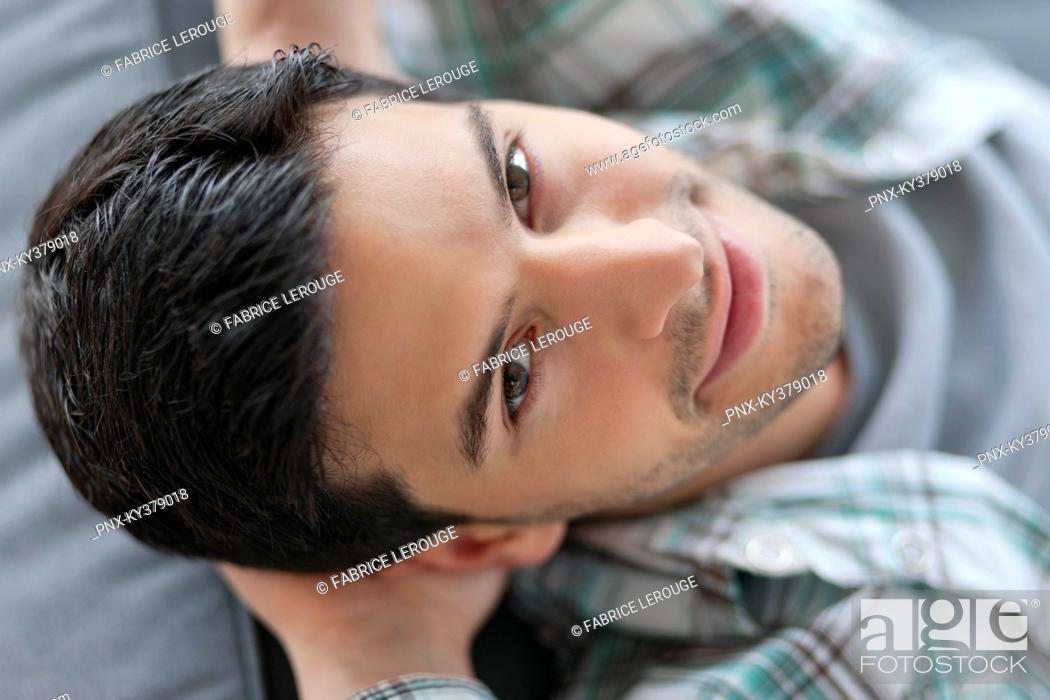 Stock Photo: Man lying on a couch and smiling.
