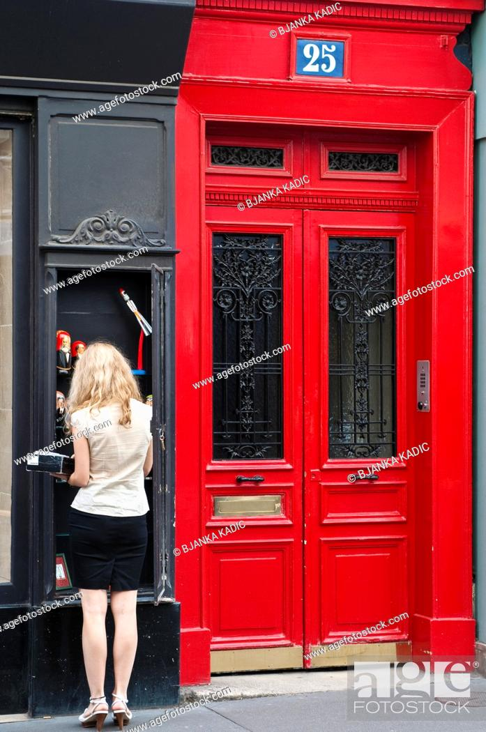 Stock Photo: Street scene with with woman and red door, St Germain des Pres, Paris, France.