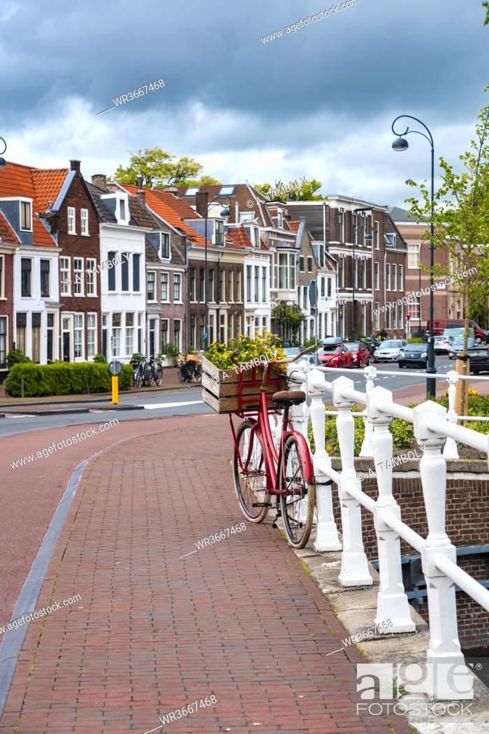 Stock Photo: Netherlands, North Holland, Haarlem, Bicycle parked along railing of canal bridge with houses alongHooimarktstreet in background.