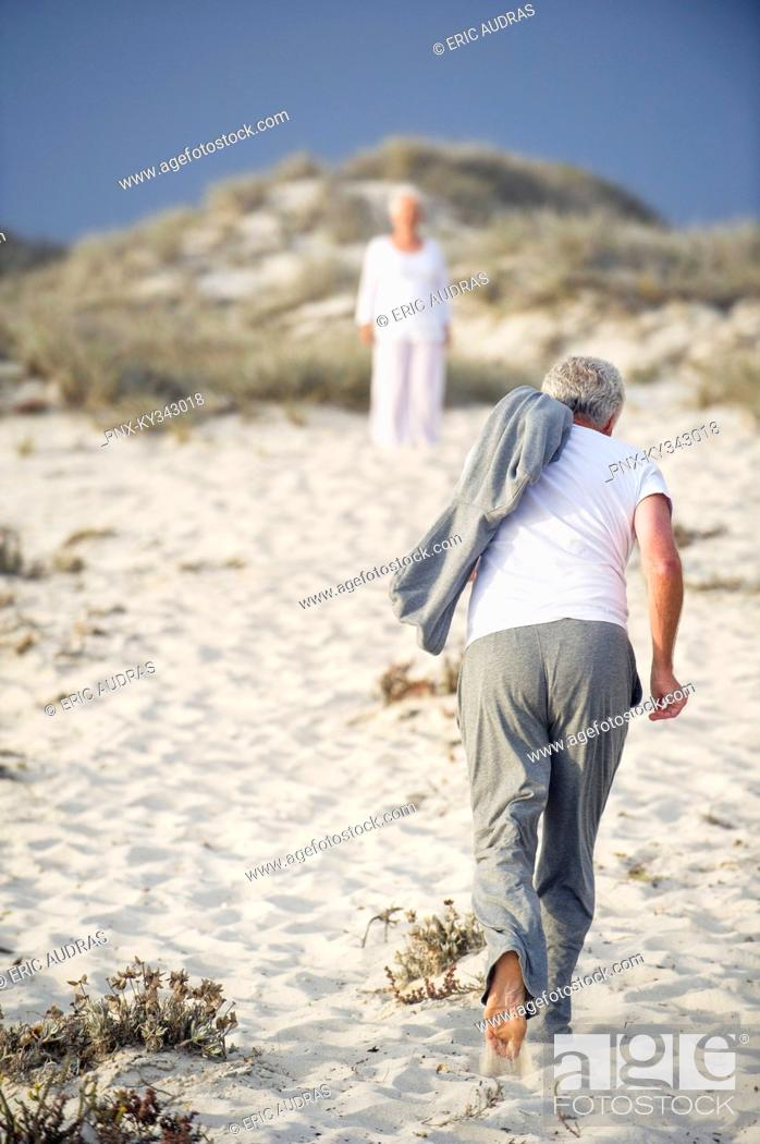 Stock Photo: Rear view of a senior man running towards a woman standing in the background.