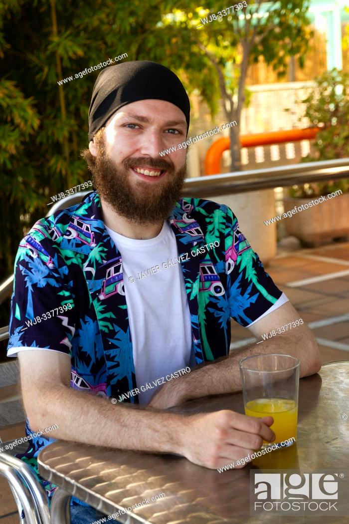 Stock Photo: portrait of happy young man with beard and headscarf while having a soda on a terrace.