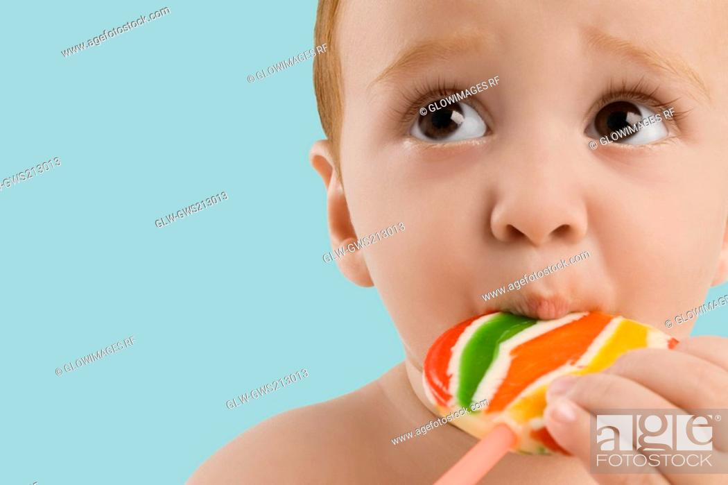 Stock Photo: Close-up of a boy licking a lollipop.