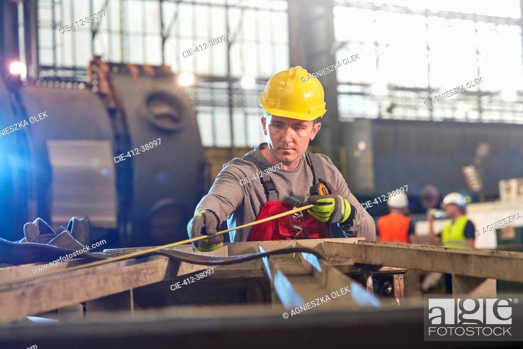 Imagen: Male worker with tape measure measuring steel in factory.