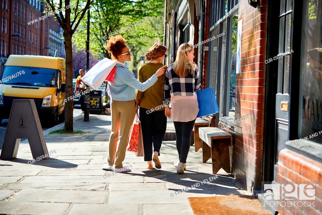 Imagen: Rear view of women carrying shopping bags walking side by side in street looking through shop window.