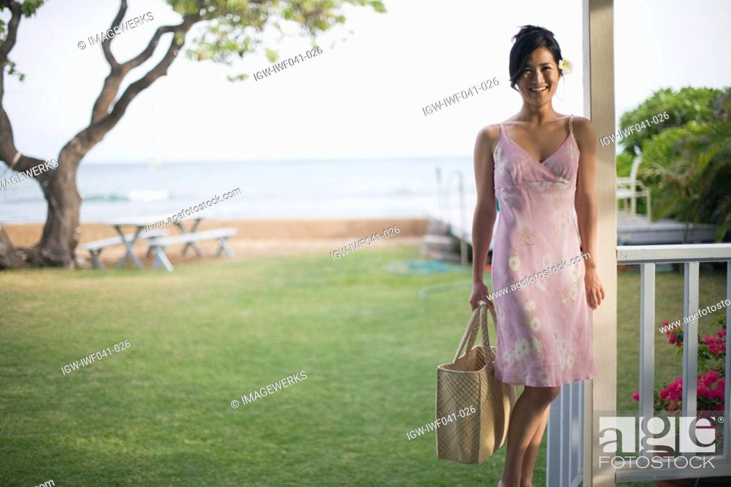 Stock Photo: A woman with bag smiling on balcony.