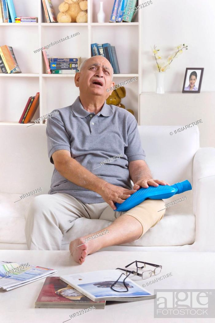 Stock Photo: Old man with hot water bag on leg.