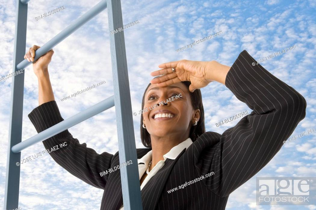 Stock Photo: African businesswoman climbing ladder in clouds.