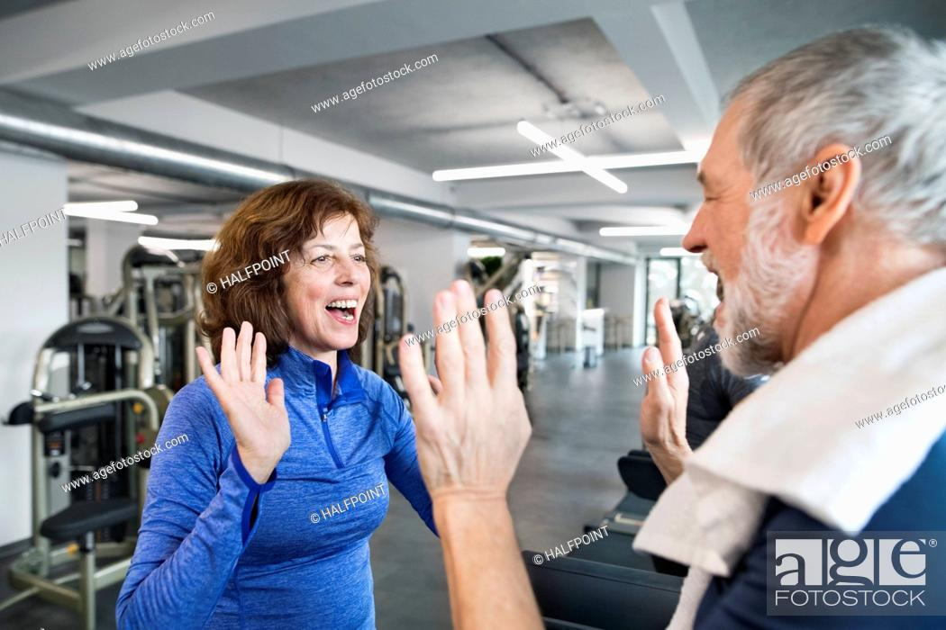 Stock Photo: Happy senior man and woman high fiving after working out in gym.