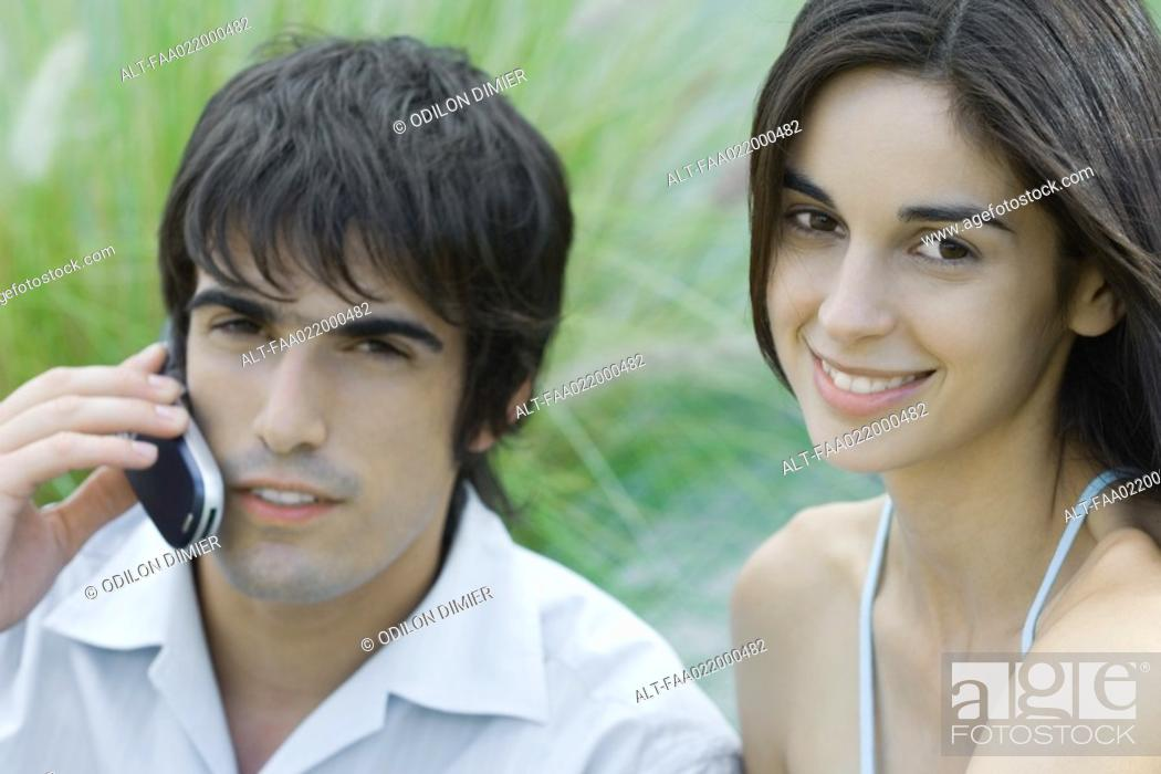 Stock Photo: Young couple, woman looking at camera, man using cell phone, head and shoulders, portrait.