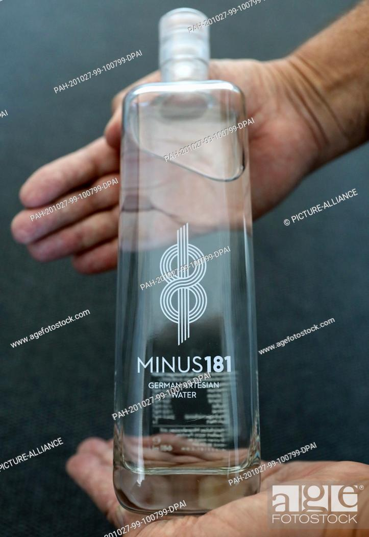 """Stock Photo: 27 October 2020, Mecklenburg-Western Pomerania, Rostock: A man holds a bottle of luxury mineral water of the brand """"""""Minus 181"""""""" for about 20 euros from Parchim."""