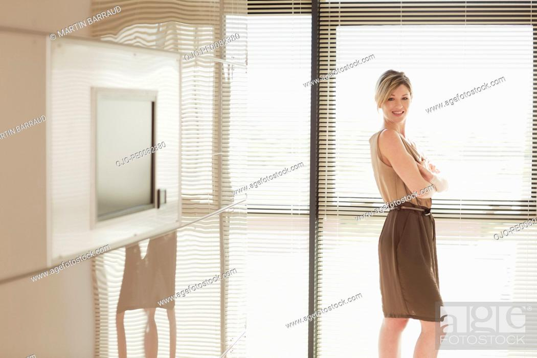 Stock Photo: Portrait of smiling businesswoman in sunny conference room.
