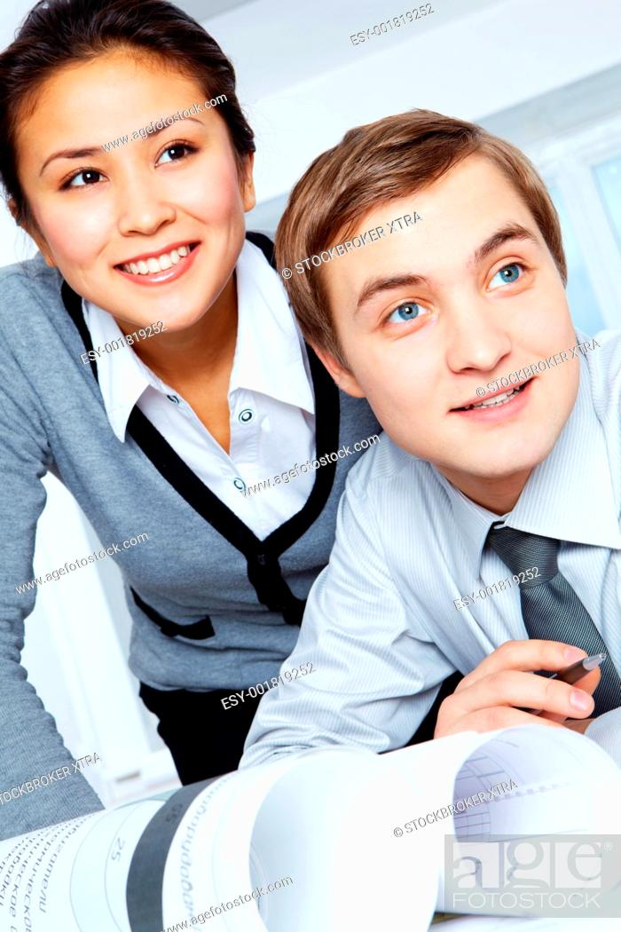 Stock Photo: Successful colleagues looking aside with smiles during work.