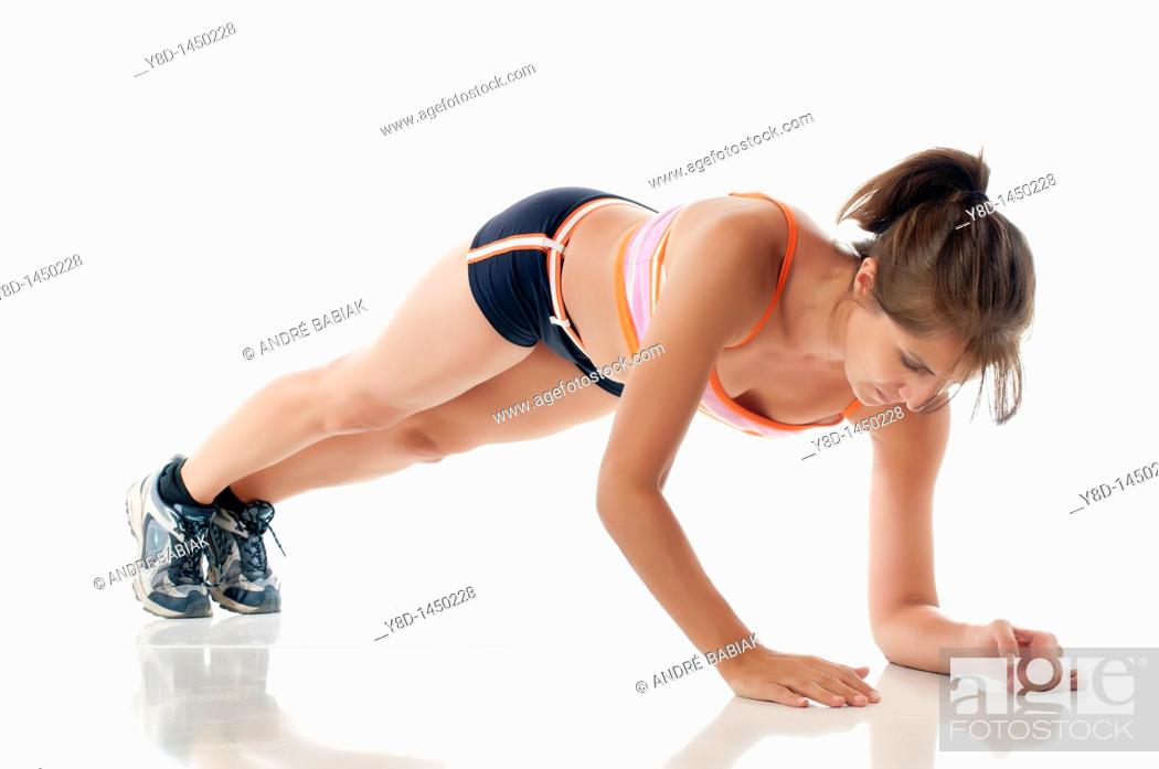 Stock Photo: Working out - Woman doing fitness exercise on white floor.