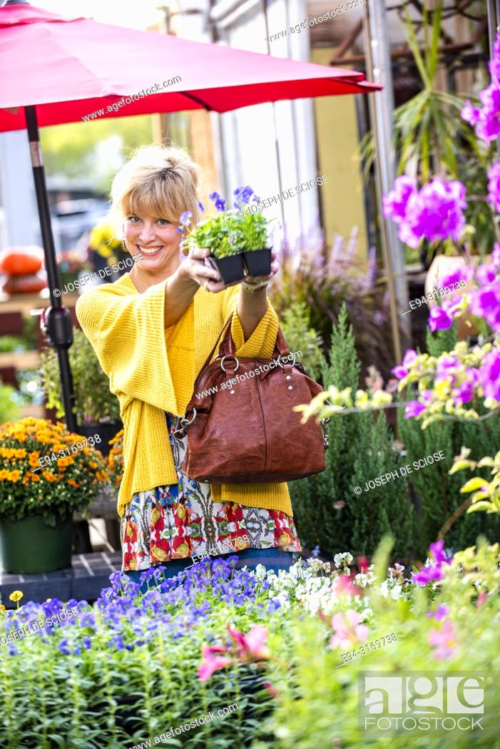 Stock Photo: A pretty 42 year old blond woman shopping at a garden store holding a 6 pack of pansies.