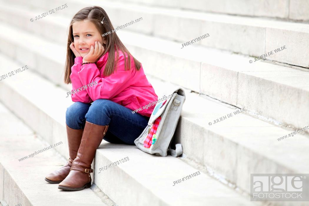 Stock Photo: Girl sitting on the steps and thinking.