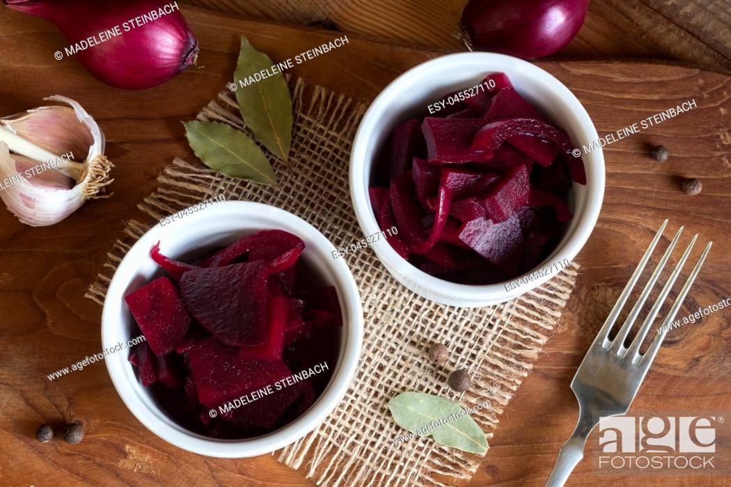 Stock Photo: Fermented red beet with onions in two round bowls, with garlic, purple onions, allspice and bay leaf in the background, top view.