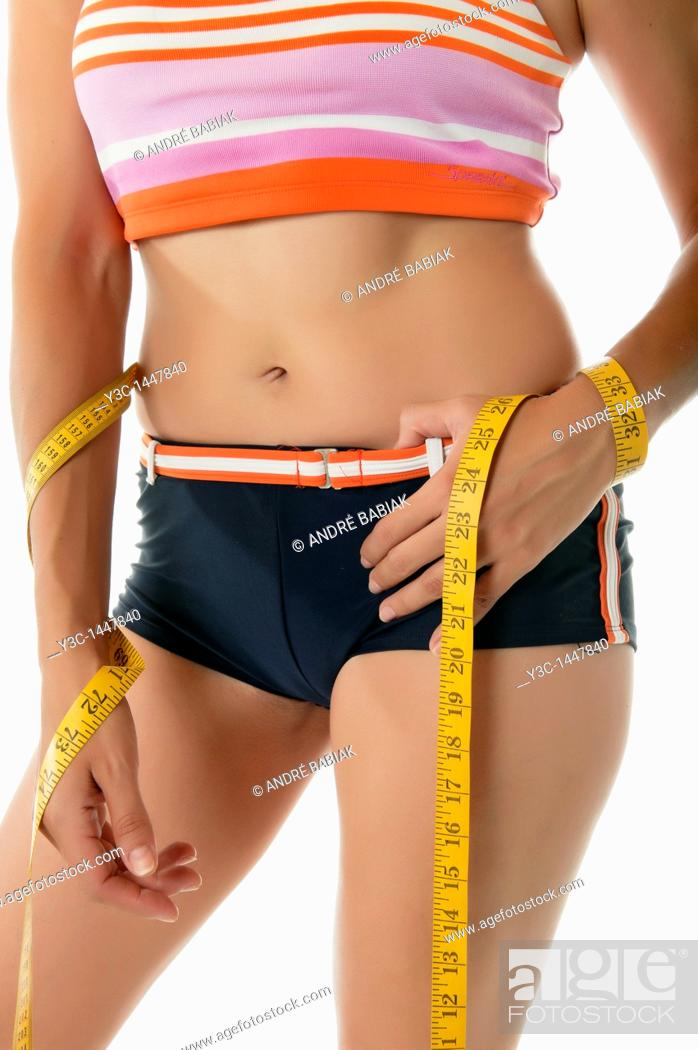 Stock Photo: Woman measuring waistline.