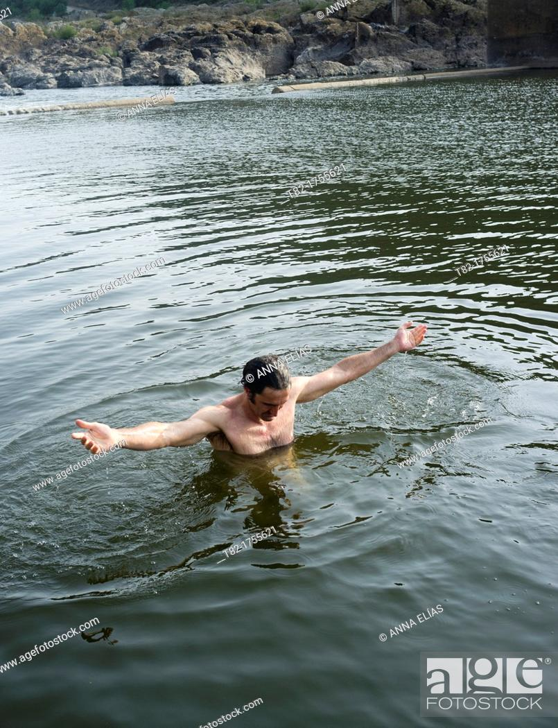 Stock Photo: shirtless young man in the water of a river, Alentejo, Portugal.