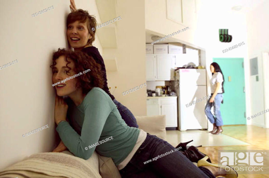 Stock Photo: Women listening at wall.