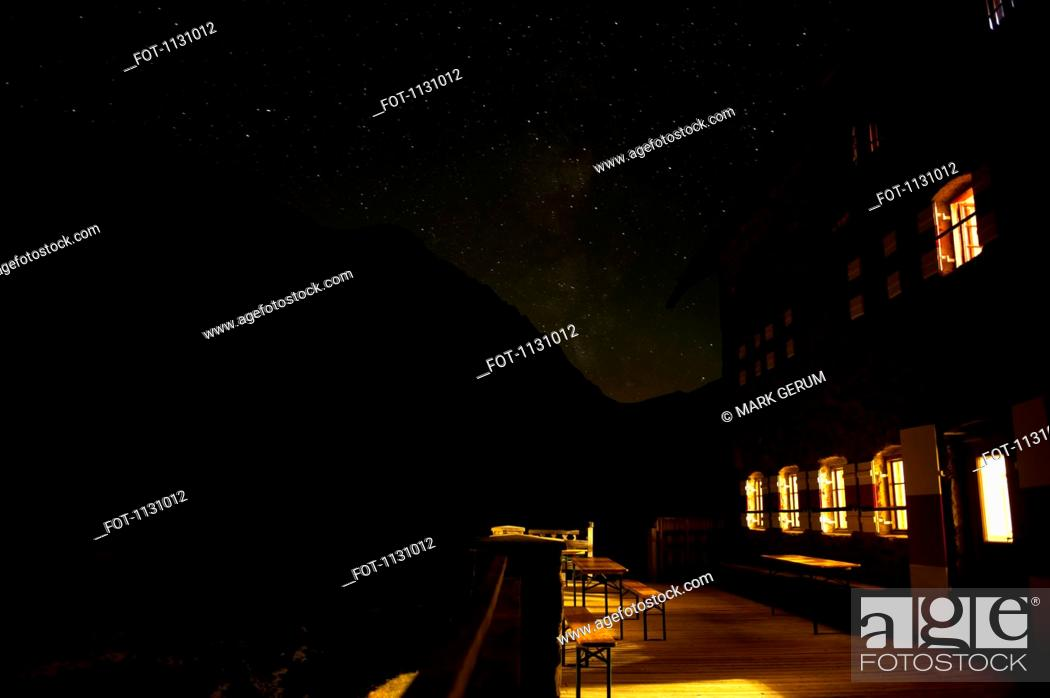Stock Photo: An illuminated building against a silhouetted mountain and starry sky.