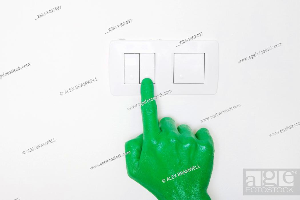 Stock Photo: A green hand switching on a light.