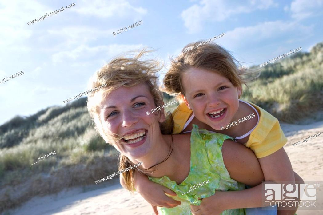 Stock Photo: Portrait of mother piggybacking daughter.