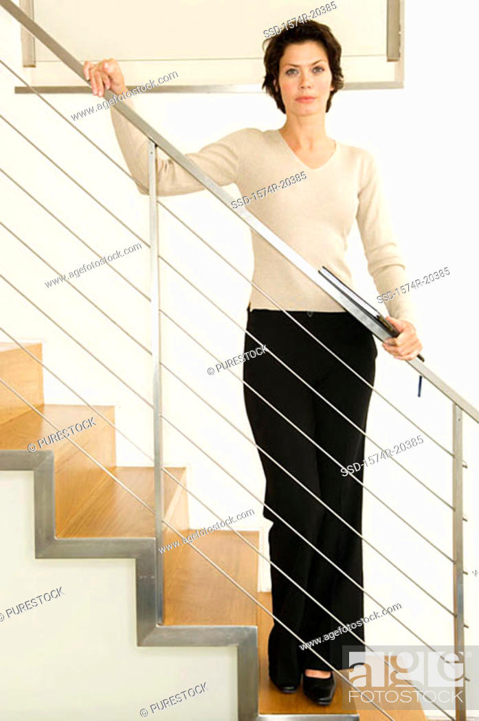 Stock Photo: Businesswoman standing on a staircase.