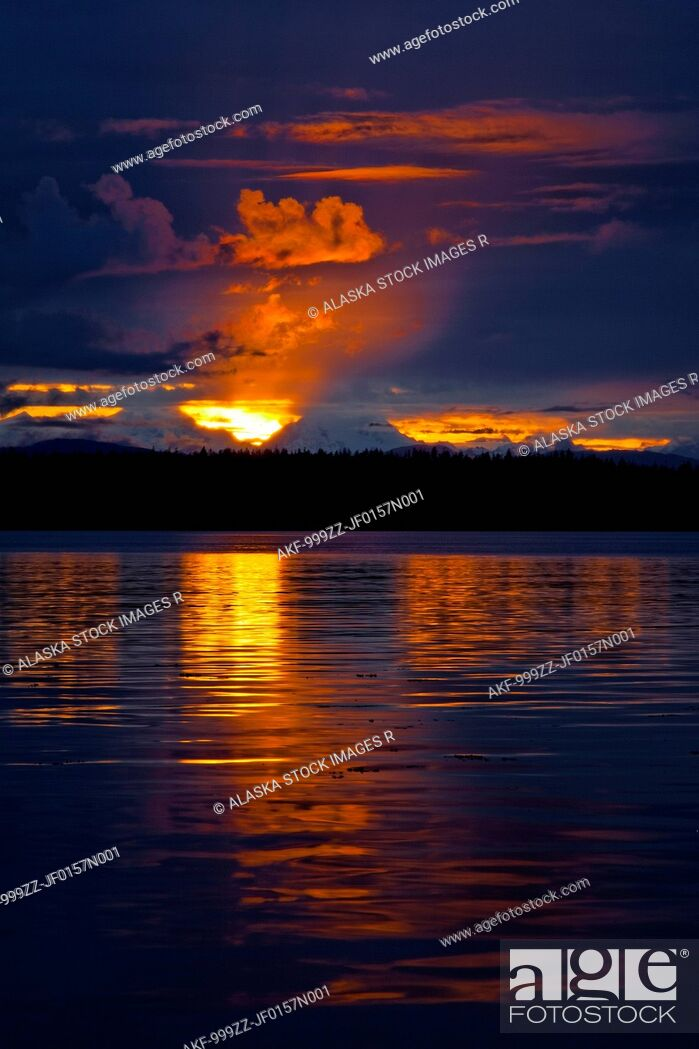 Stock Photo: Dramatic sunset behind Fairweather Mountains and reflecting off water in Bartlett Cove, Glacier Bay National Park & Preserve, Southeast Alaska, Summer.