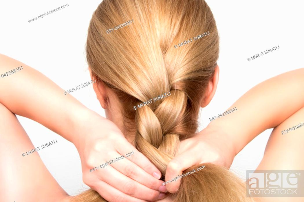 Stock Photo: Gorgeous blonde woman braids her hair from behind.