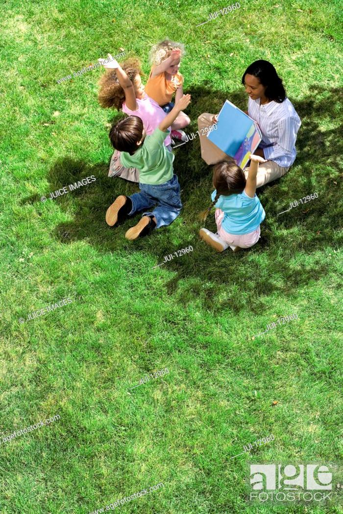 Stock Photo: Teacher reading book to children 5-9 outdoors, elevated view.
