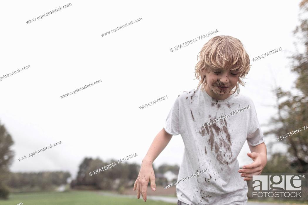 Stock Photo: Portrait of blond boy with dirty face and t-shirt after jumping into a puddle.