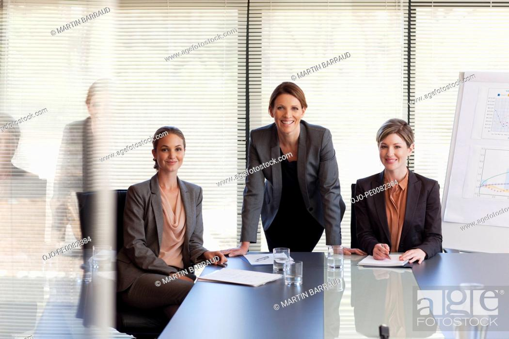 Stock Photo: Portrait of smiling businesswomen at table in conference room.