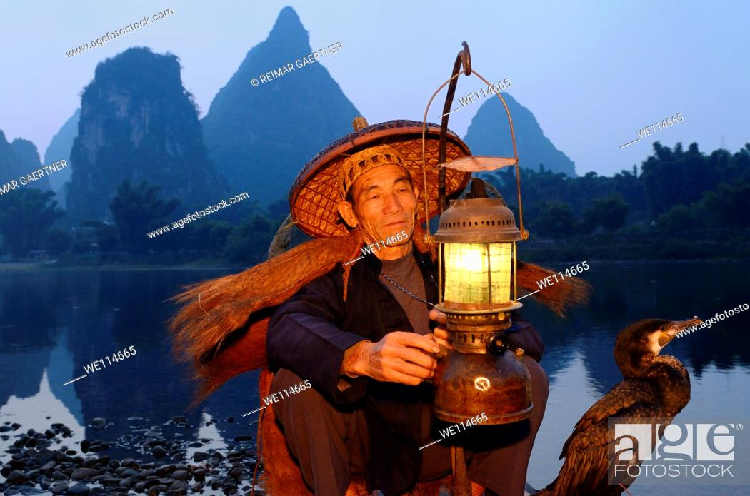 Stock Photo: Cormorant fisherman with lamp and bird on bamboo raft at dawn on the shore of the Li river Yangshuo China.