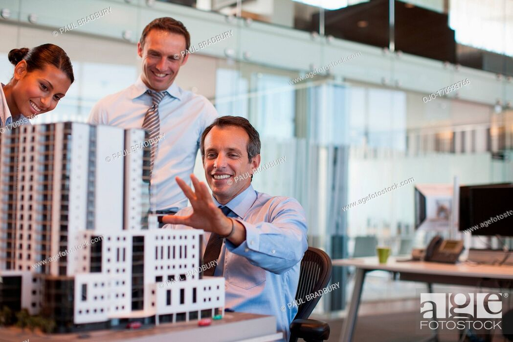 Stock Photo: Business people looking at model building in office.