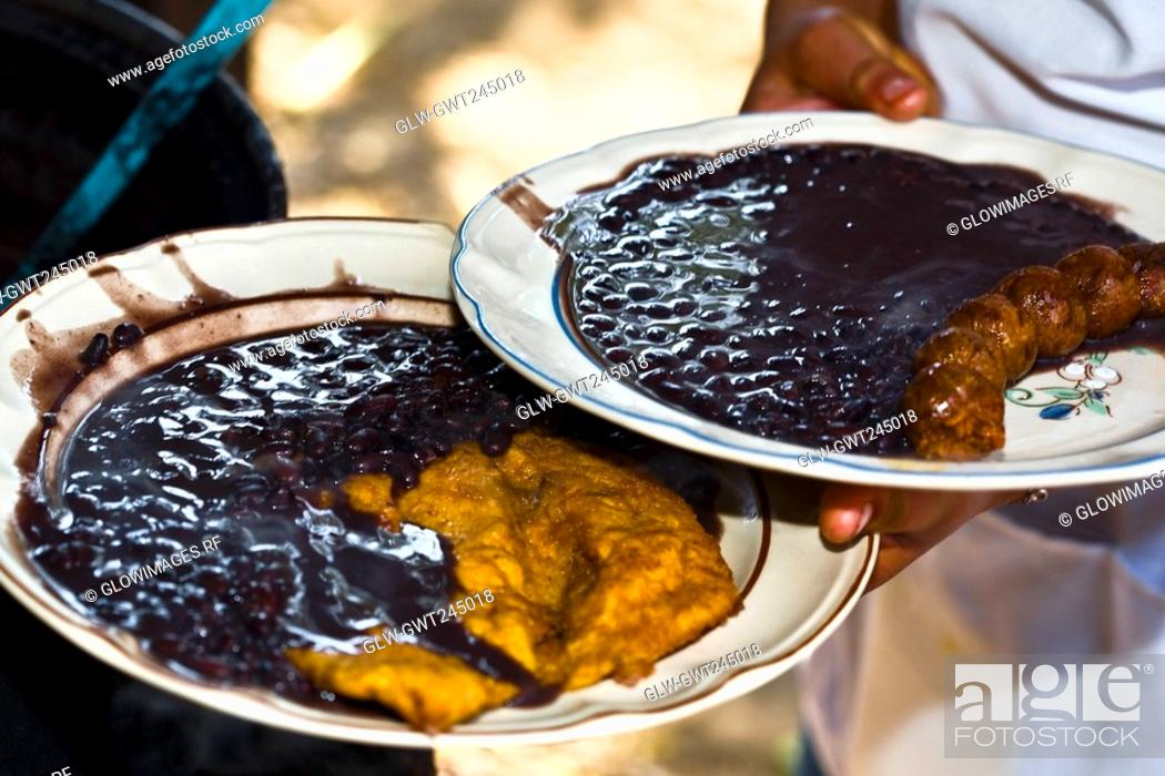 Stock Photo: Mid section view of a person holding plates of Mexican food, Santo Tomas Jalieza, Oaxaca State, Mexico.