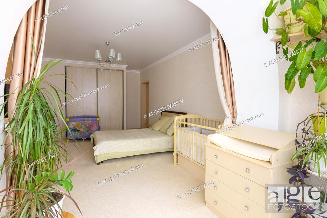 Stock Photo: View from the glazed loggia to the interior of a spacious bedroom with furniture for a newborn baby.
