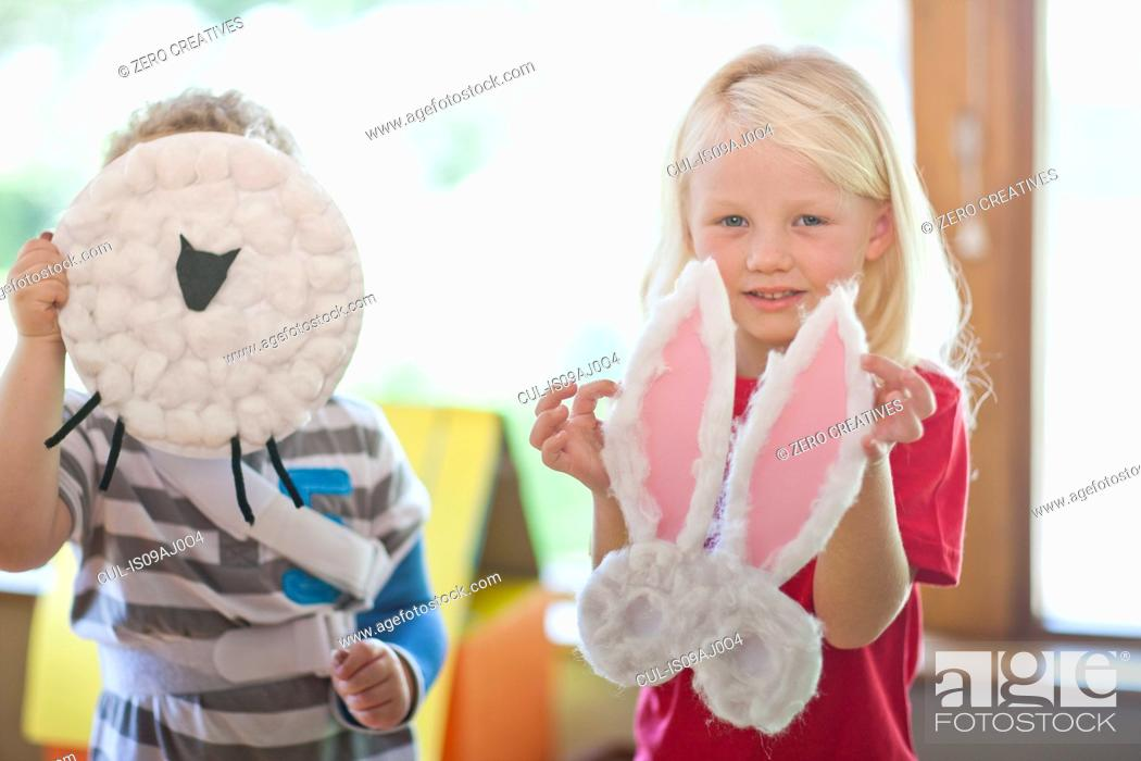Stock Photo: Boy and girl holding up sheep and rabbit creations at nursery school.