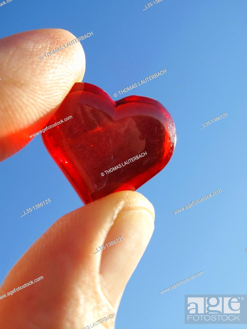 Stock Photo: Hand holding small glass heart with blue sky.
