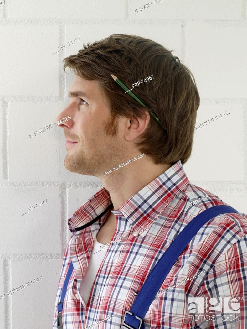 Stock Photo: Mann wearing work wear with a pencil behind his ear.
