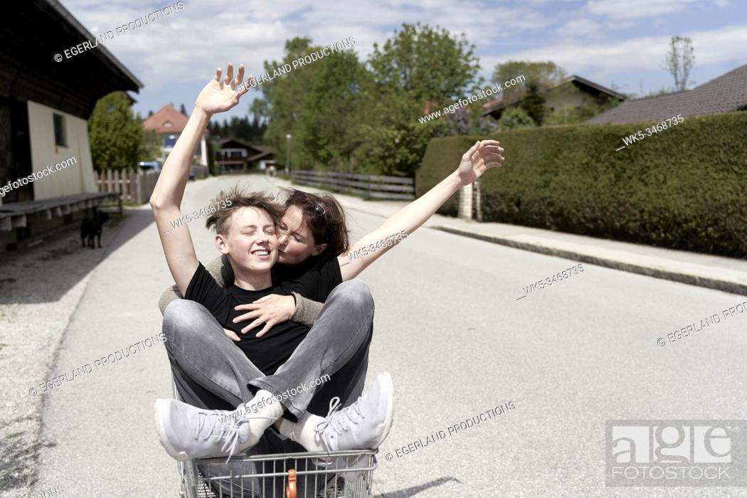 Stock Photo: Mother and son fooling around with a shopping cart, in Gaissach, Bavaria, Germany.