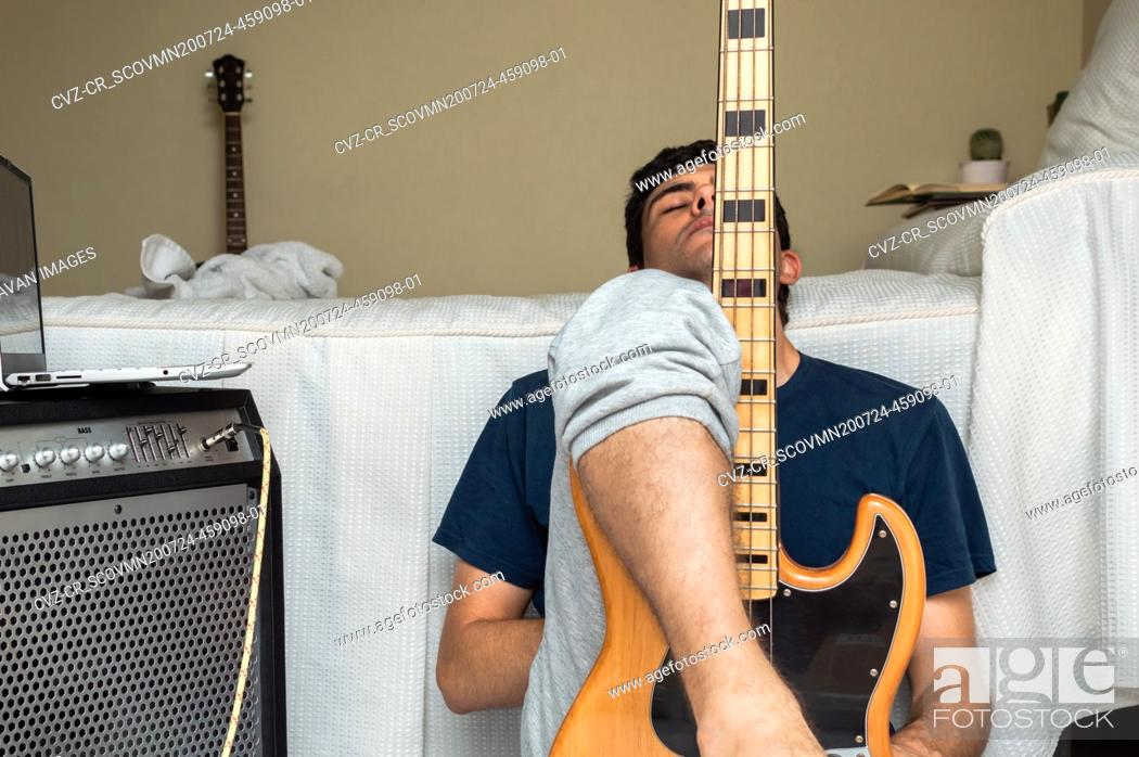 Stock Photo: Tired man takes a break after playing electric bass at home.