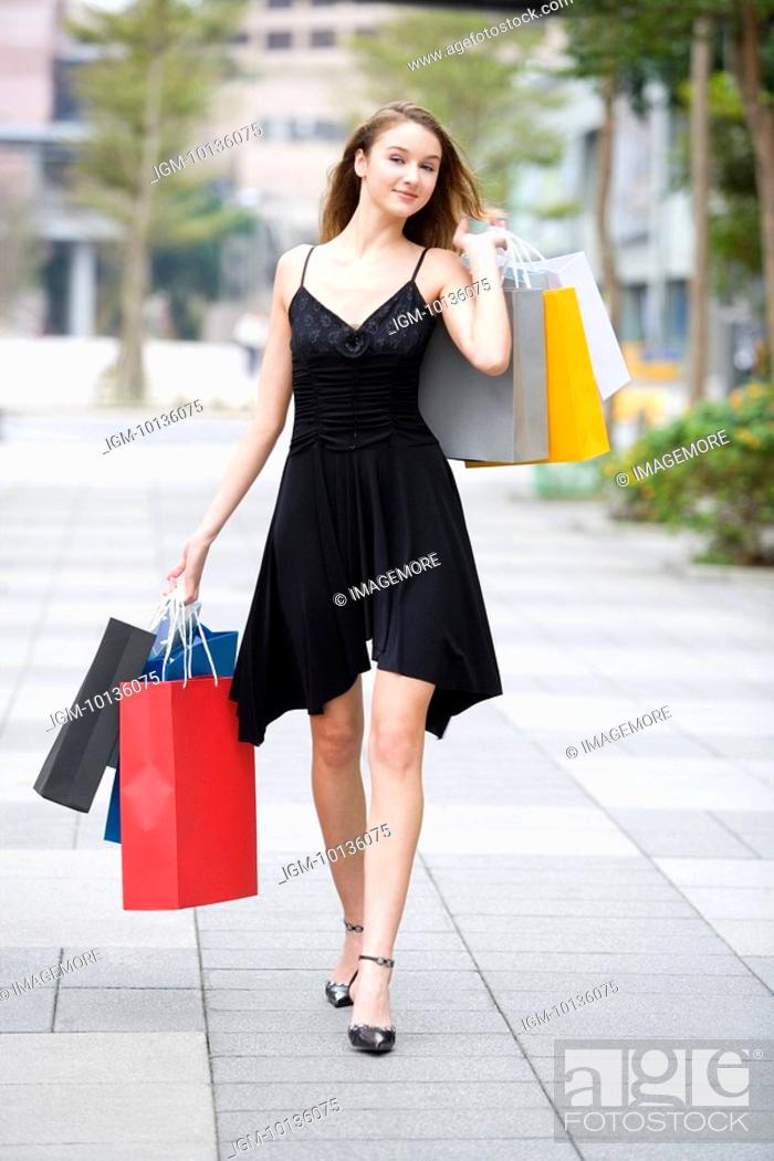 Stock Photo: Teenage girl holding shopping bags walking on street.