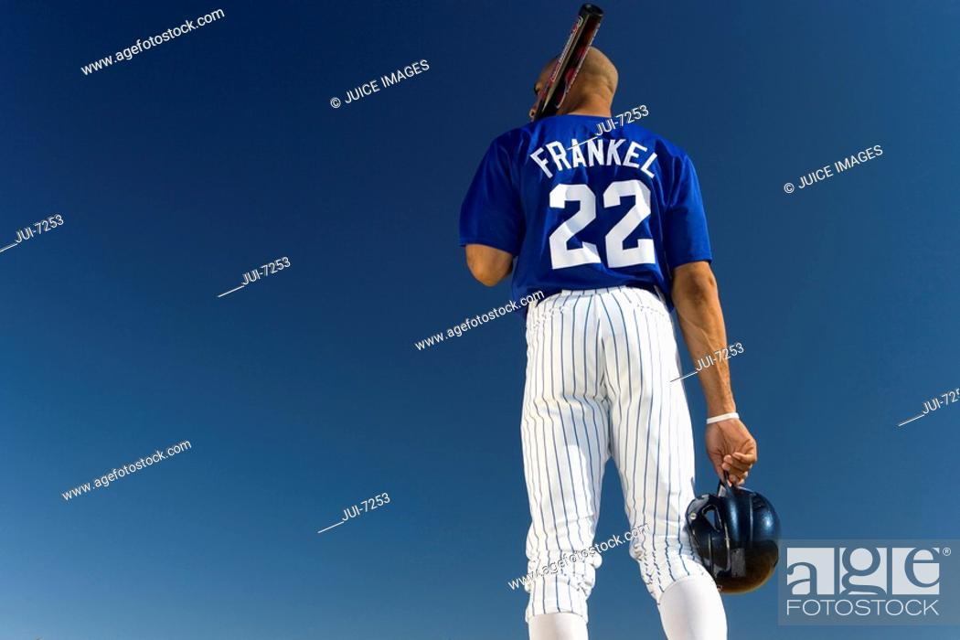 Stock Photo: Baseball player standing against clear blue sky, carrying bat on shoulder, rear view, low angle view.