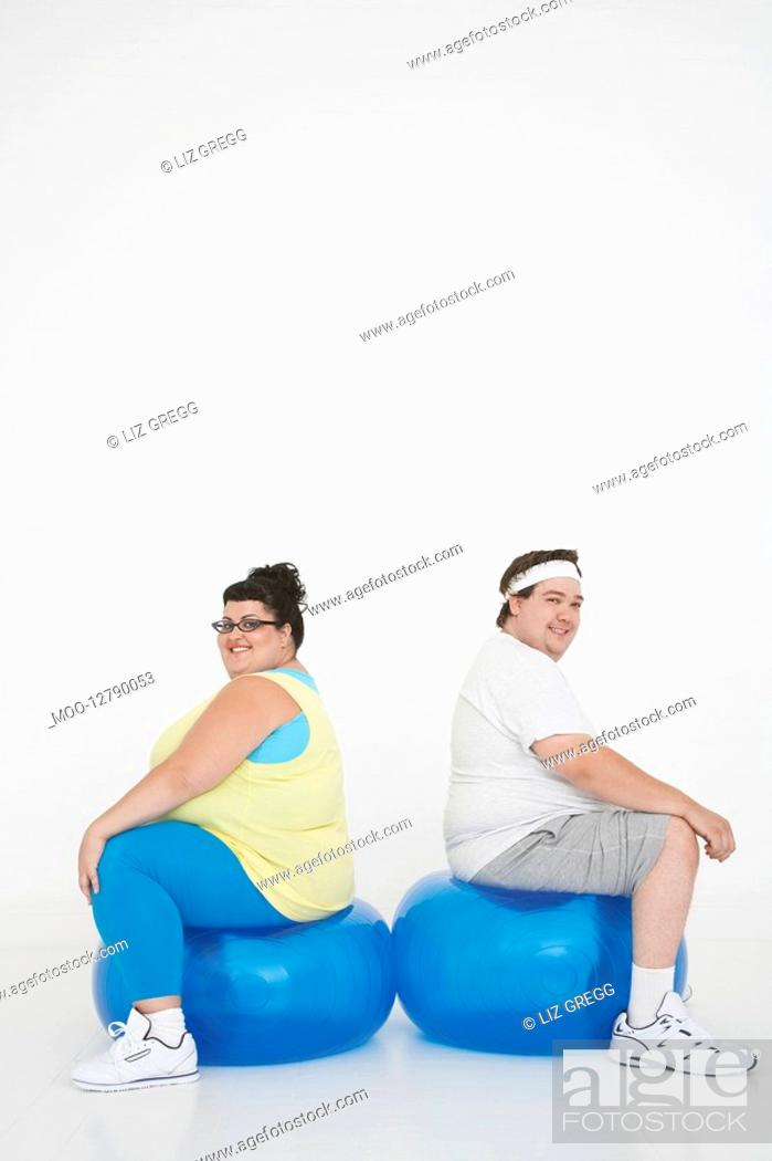 Stock Photo: Overweight man and woman sitting back to back on exercise balls portrait.